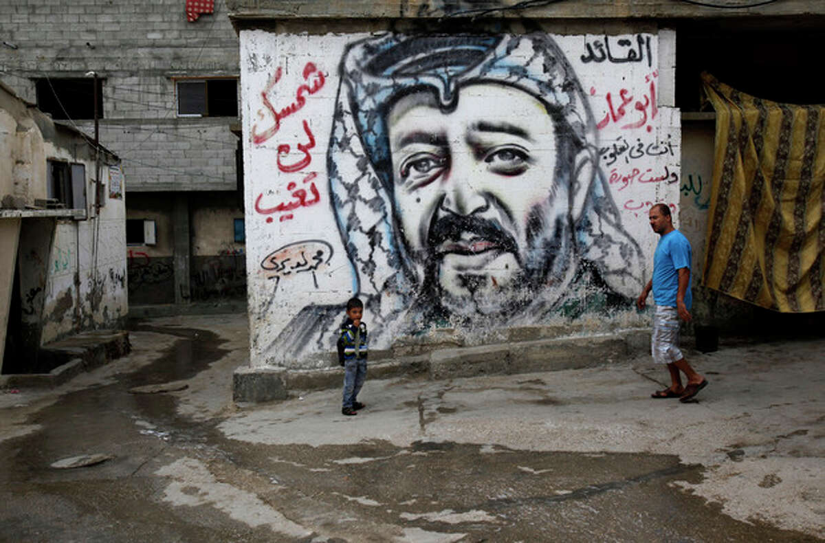"""Palestinians walk past a mural depicting late Palestinian leader Yasser Arafat at Shati Refugee Camp, in Gaza City, Thursday, Nov. 7, 2013. Swiss scientists have found evidence suggesting Yasser Arafat may have been poisoned with a radioactive substance, a TV station reported on Wednesday, prompting new allegations by his widow that the Palestinian leader was the victim of a """"shocking"""" crime. Arabic reads, """"the leader Abu Ammar, you are in our hearts, your sun will not go down."""" (AP Photo/Adel Hana)"""
