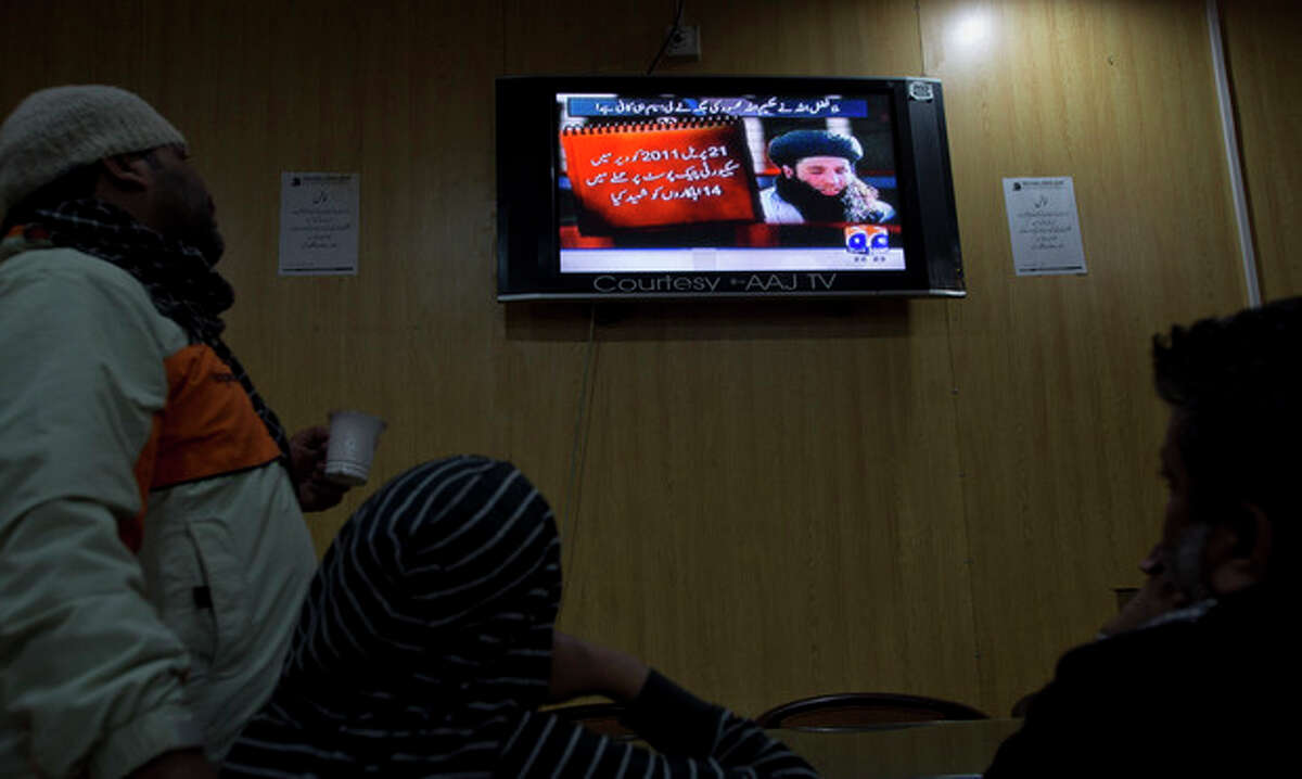 People watch a news report on TV about newly selected leader of Pakistani Taliban leader Mullah Fazlullah at a coffee shop in Islamabad, Pakistan, Thursday, Nov. 7, 2013. The ruthless commander behind the attack on teenage activist Malala Yousafzai as well as a series of bombings and beheadings was chosen Thursday as the leader of the Pakistani Taliban, nearly a week after a U.S. drone strike killed the previous chief. The Arabic on the TV news report reads,