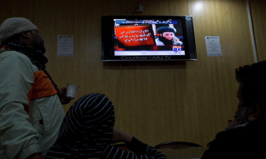 "People watch a news report on TV about newly selected leader of Pakistani Taliban leader Mullah Fazlullah at a coffee shop in Islamabad, Pakistan, Thursday, Nov. 7, 2013. The ruthless commander behind the attack on teenage activist Malala Yousafzai as well as a series of bombings and beheadings was chosen Thursday as the leader of the Pakistani Taliban, nearly a week after a U.S. drone strike killed the previous chief. The Arabic on the TV news report reads, ""On April 21, 2011, fourteen troops were killed in an attack on a checkpoint in Dir."" (AP Photo/B.K. Bangash) / AP"