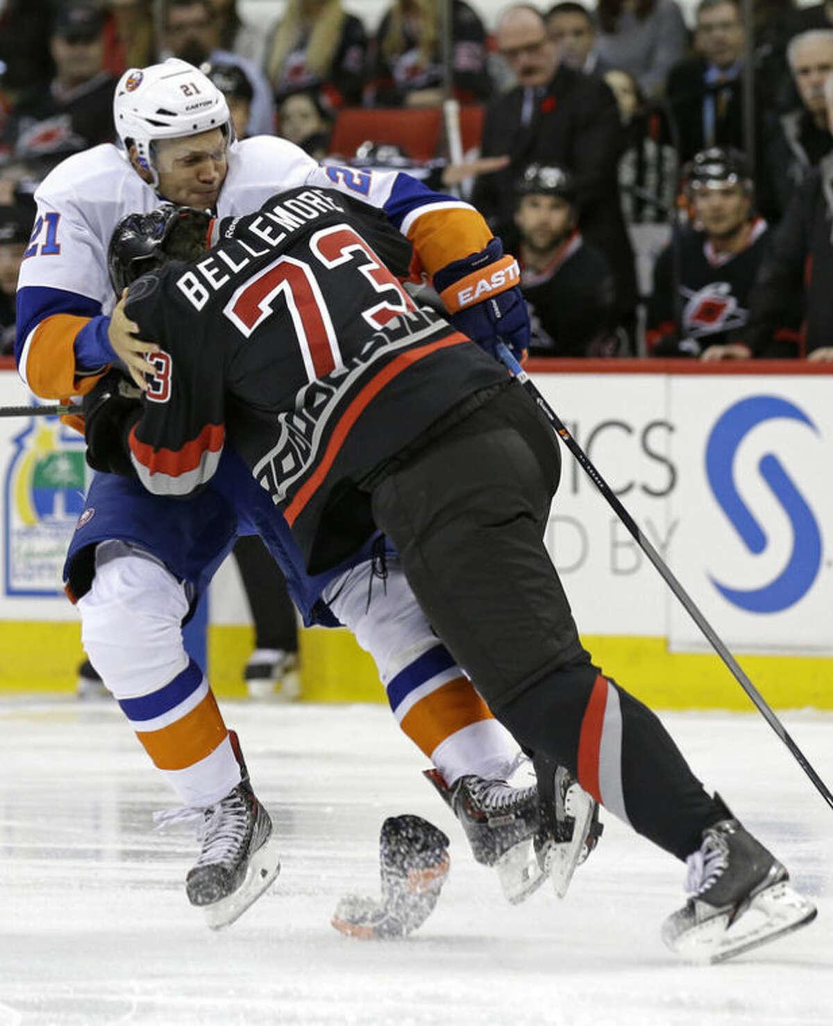 Carolina Hurricanes' Brett Bellemore (73) checks New York Islanders' Kyle Okposo (21) during the first period of an NHL hockey game in Raleigh, N.C., Thursday, Nov. 7, 2013. (AP Photo/Gerry Broome)