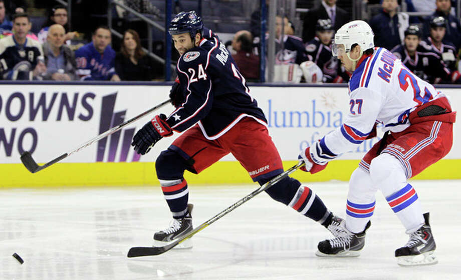 New York Rangers' Ryan McDonagh, right, and Columbus Blue Jackets' Derek MacKenzie chase a loose puck during the second period of an NHL hockey game Thursday, Nov. 7, 2013, in Columbus, Ohio. (AP Photo/Jay LaPrete) / FR52593 AP