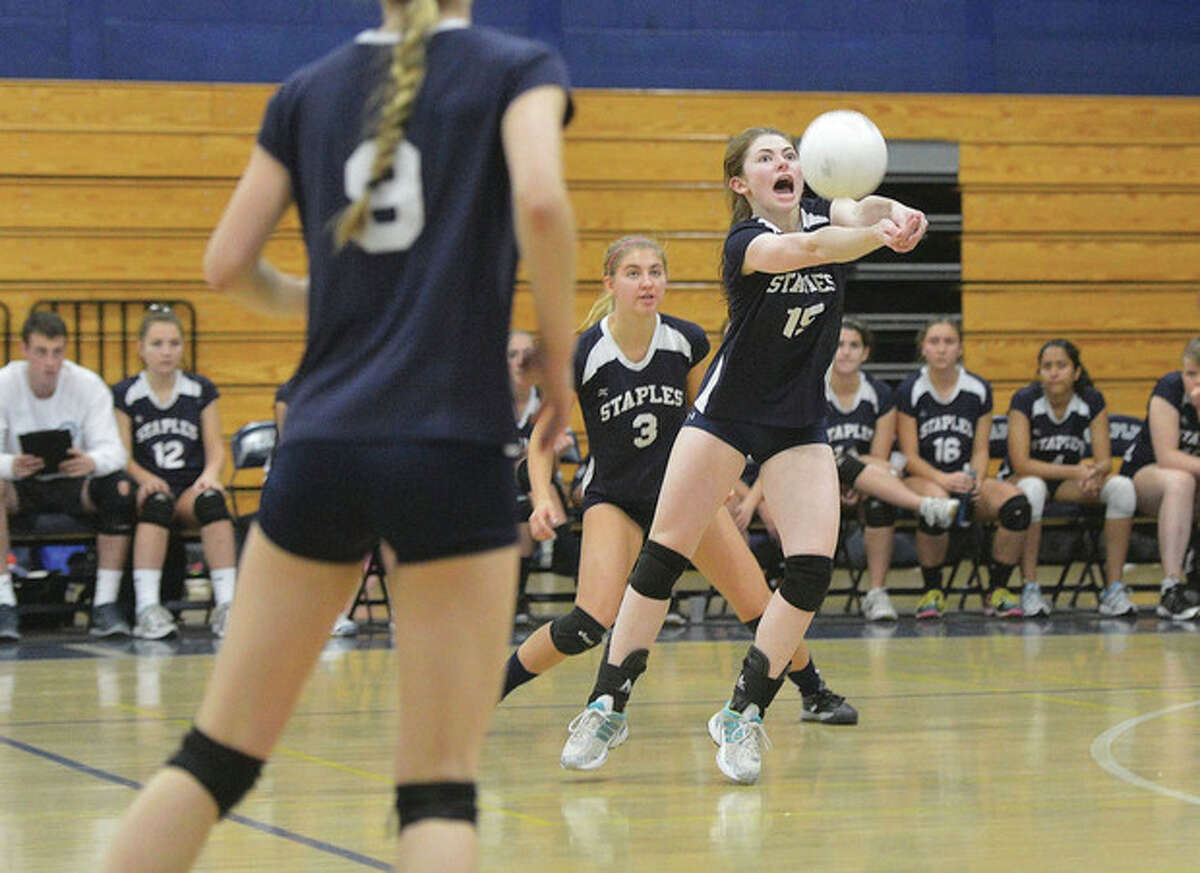 Hour photo/Alex von Kleydorff Ariana Sherman of Staples stretches to bump the ball during Thursday's state tournament match against Danbury. The second-seeded Wreckers won, 3-1.