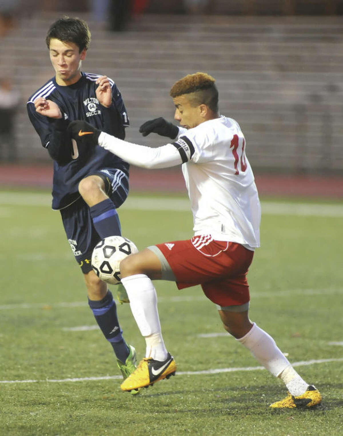 Hour photo/John Nash Wilton's jack Brandt, left, and Conard's Matheus Souza brace for a collision as they play the ball during Thursday's CIAC Class LL second round playoff game. Conard won the game, 3-1.