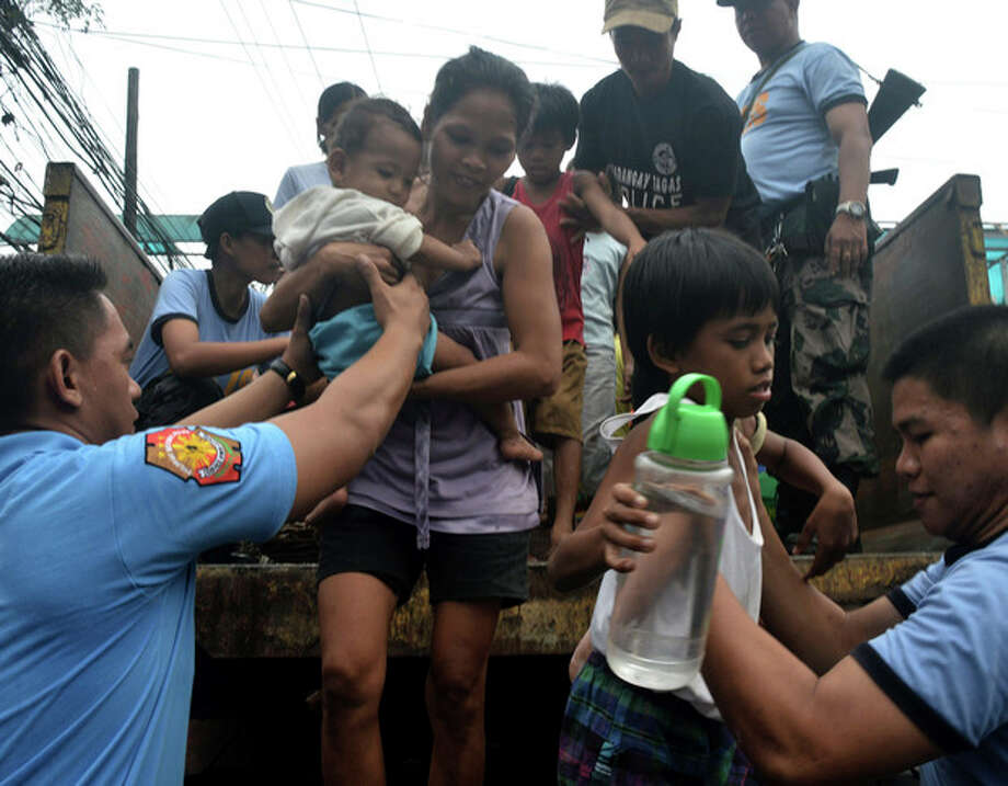 In this Thursday, Nov. 7, 2013 photo, residents living near the slopes of Mayon volcano are evacuated to public schools by police in anticipation of the powerful typhoon Haiyan that threatened Albay province and several provinces in central Philippines. The typhoon, one of the most powerful typhoons ever recorded, slammed into the Philippines early Friday, with one weather expert warning of catastrophic damage. (AP Photo/Nelson Salting) / AP