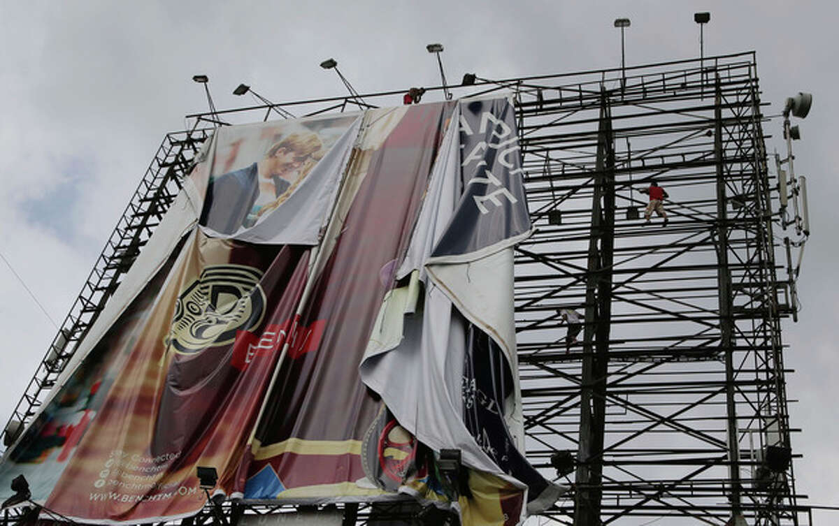 Filipino workers bring down a giant billboard along a busy highway as they prepare for the possible effects of powerful Typhoon Haiyan in suburban Makati, south of Manila, Philippines Thursday, Nov. 7, 2013. Philippine officials say thousands of villagers, including those from a central province devastated recently by an earthquake, are being evacuated ahead of the arrival of one of Asia's most powerful typhoons this year. (AP Photo/Aaron Favila)