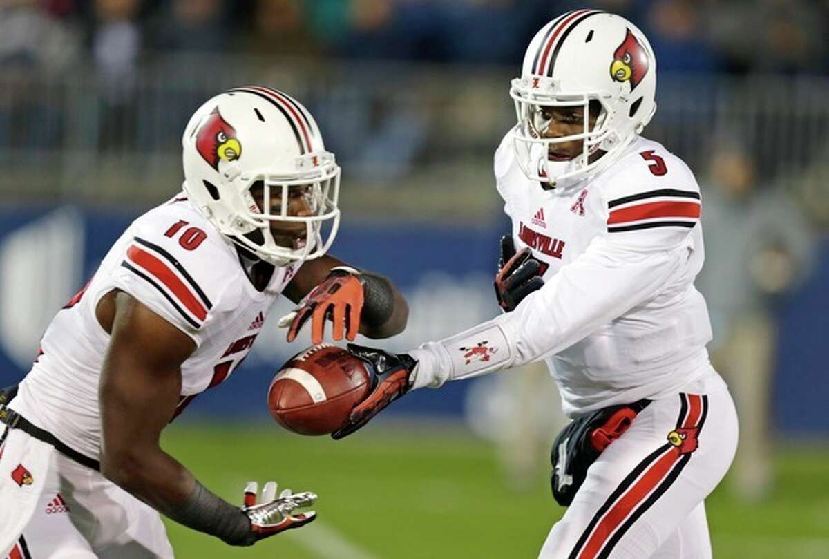 Louisville quarterback Teddy Bridgewater (5) hands off to Louisville Cardinals running back Dominique Brown (10) against Connecticut during the first half of an NCAA college football game, in East Hartford, Conn., Friday, Nov. 8, 2013. (AP Photo/Charles Krupa)