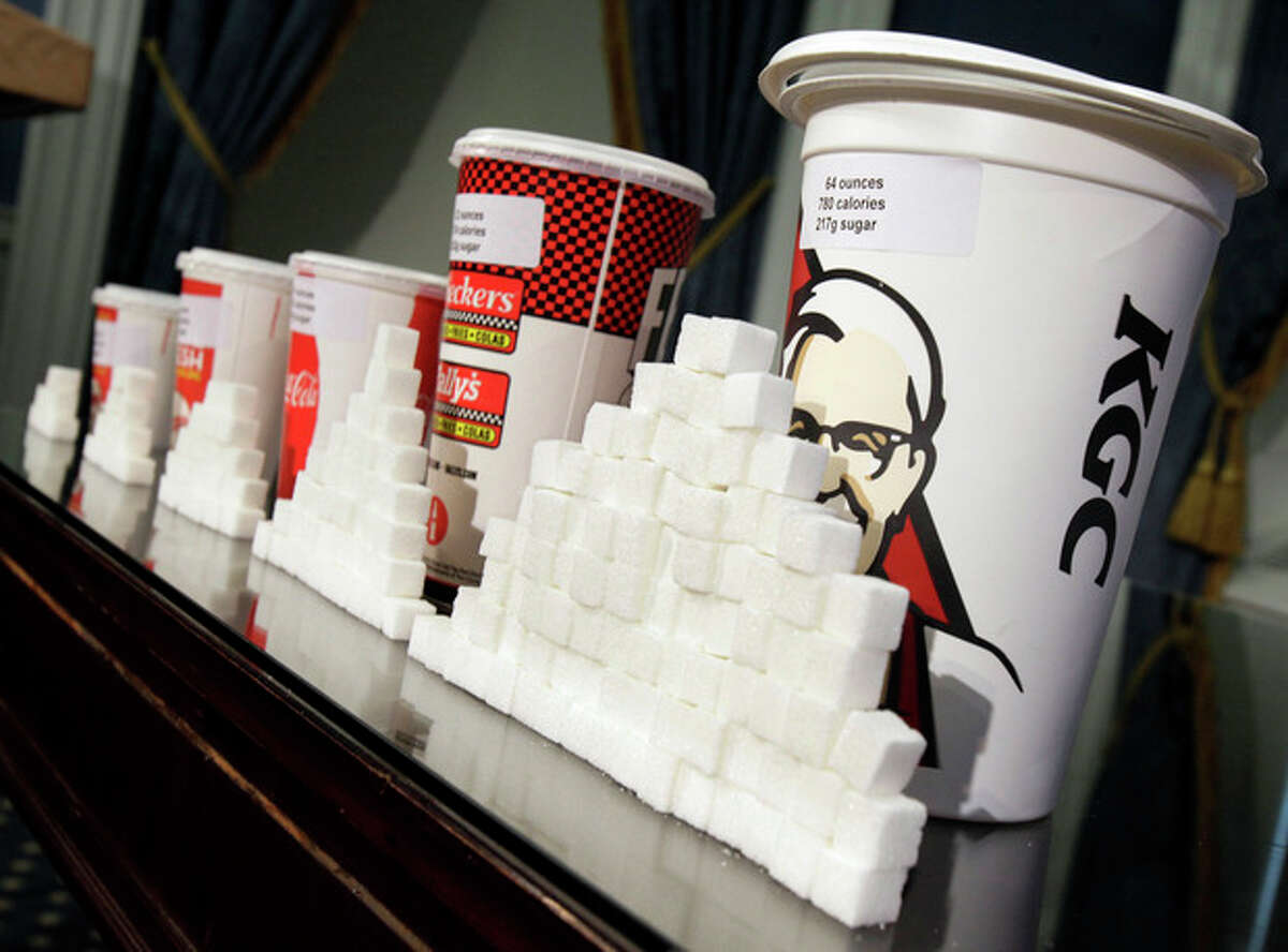 FILE - This May 31, 2012 file photo shows a display of various size soft drink cups next to stacks of sugar cubes at a news conference at New York's City Hall. It?'s one of our most personal daily decisions: what to eat or drink. Maybe inhale. Does banning trans fat from our food mean the government is getting serious about cracking down on all sorts of other unhealthy stuff: Soda? Salt? Cigarettes? Alcohol? Probably not. In fact, in some states, they?'re easing the way for marijuana. (AP Photo/Richard Drew, File)