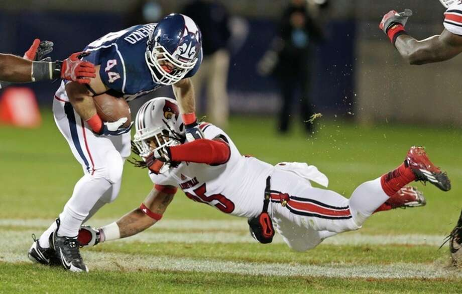 Louisville safety Calvin Pryor, right, dives as he tries to tackle Connecticut running back Max DeLorenzo (44) during the first half of an NCAA college football game, in East Hartford, Conn., Friday, Nov. 8, 2013. (AP Photo/Charles Krupa) / AP