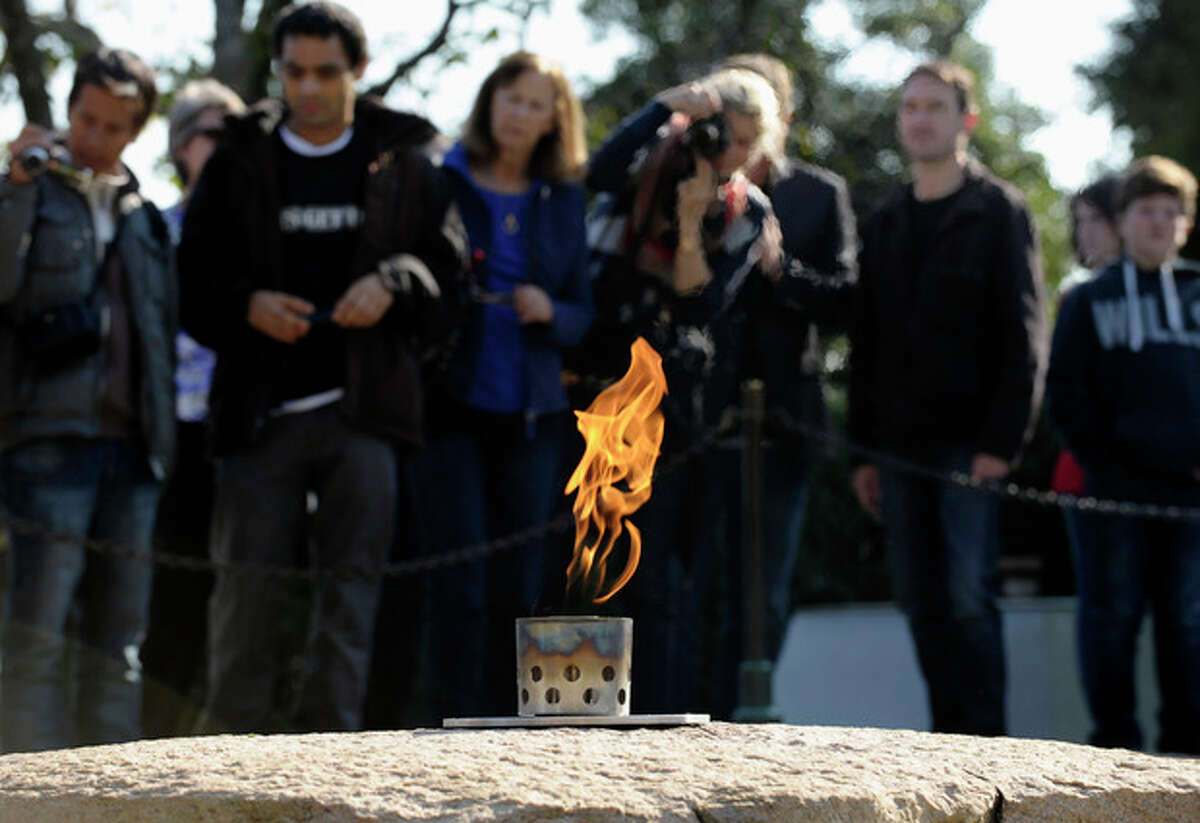 ADVANCE FOR USE SUNDAY, NOV. 10, 2013 AND THEREAFTER - FILE - In this Tuesday, Oct. 29, 2013 file photo, visitors stand near the eternal flame at the grave site of U.S. President John F. Kennedy at the Arlington National Cemetery in Arlington, Va. The cemetery transferred the flame from a temporary burner to the restored permanent eternal flame that is part of a memorial to the 35th president. Repairs began in April 2013 to replace components of the eternal flame's burner. (AP Photo/Susan Walsh)