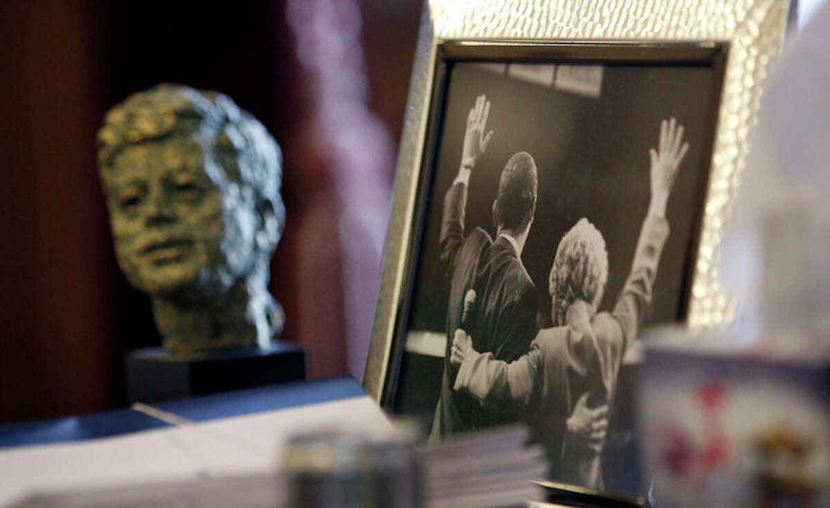ADVANCE FOR USE SUNDAY, NOV. 10, 2013 AND THEREAFTER - FILE - In this Dec. 11, 2012 file photo, a bust of former U.S. President John F. Kennedy sits on the desk of Gov. Chris Gregoire near a photo of Gregoire and U.S. President Barack Obama, in Olympia, Wash. Lisa Pease, a researcher who has studied 1960s assassinations extensively, said at an October 2013 assassination symposium in Pittsburgh,