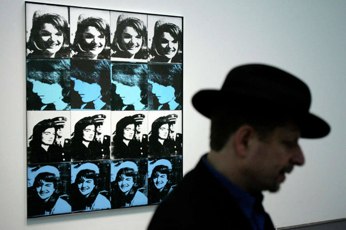 """ADVANCE FOR USE SUNDAY, NOV. 10, 2013 AND THEREAFTER - FILE - In this Friday, March 17, 2006 file photo, a visitor talks about Andy Warhol's """"Sixteen Jackies"""" during a preview at the Museum of Contemporary Art in Chicago. The work features images of Jackie Kennedy shortly before and after President John F. Kennedy's assassination. (AP Photo/M. Spencer Green)"""