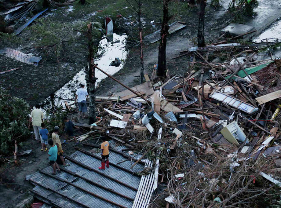 "Residents sift through the rubble of their damaged house following a powerful typhoon that hit Tacloban city, in Leyte province, central Philippines Saturday, Nov. 9, 2013. The central Philippine city of Tacloban was in ruins Saturday, a day after being ravaged by Typhoon Haiyan, one of the strongest typhoons on record, as horrified residents spoke of storm surges as high as trees and authorities said they were expecting a ""very high number of fatalities."" (AP Photo/Bullit Marquez) / AP"
