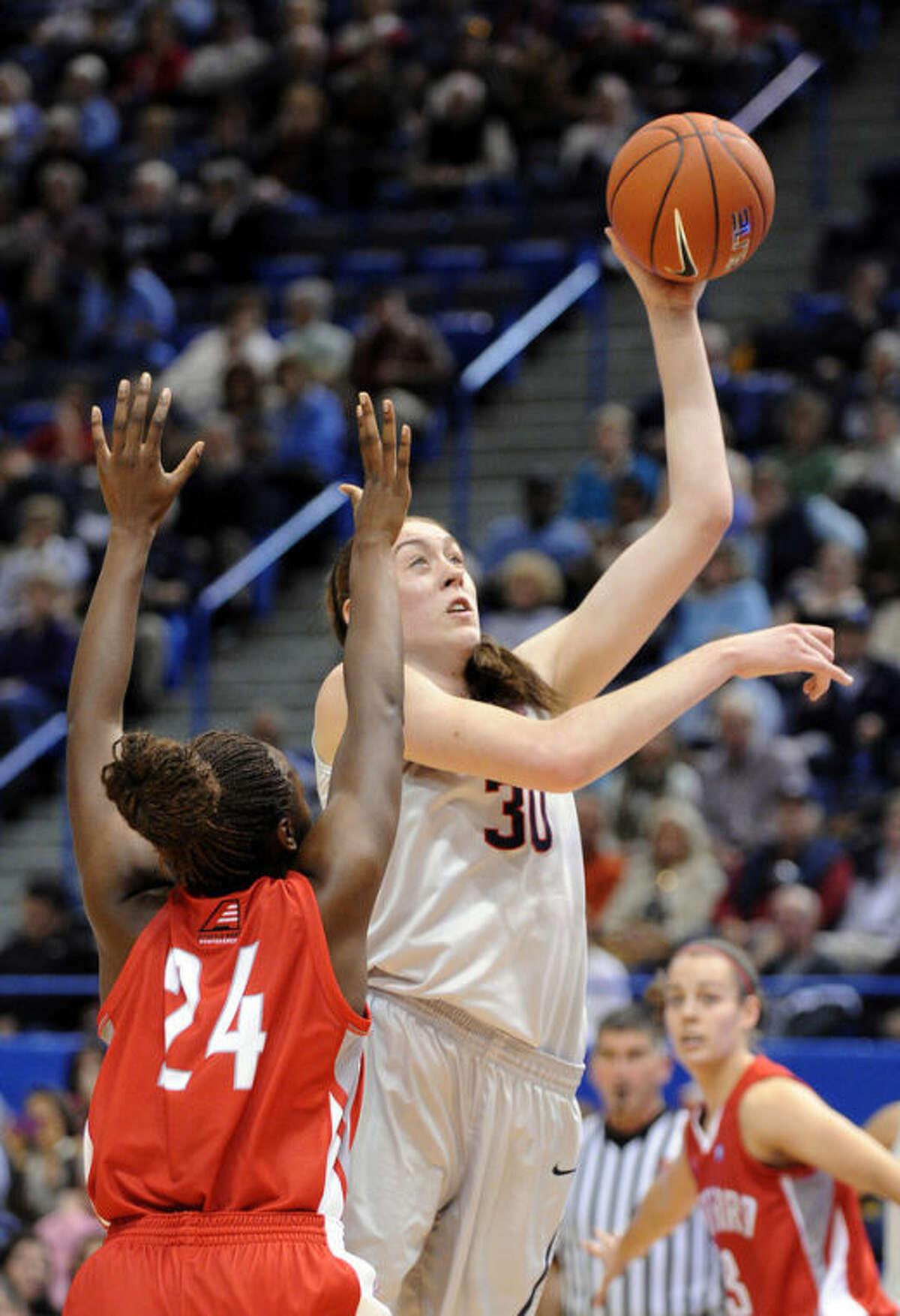 Connecticut forward Breanna Stewart (30) shoots over Hartford forward Alyssa Reaves (24) during the first half of an NCAA college basketball game in Hartford, Conn., on Saturday, Nov. 9, 2013. (AP Photo/Fred Beckham)