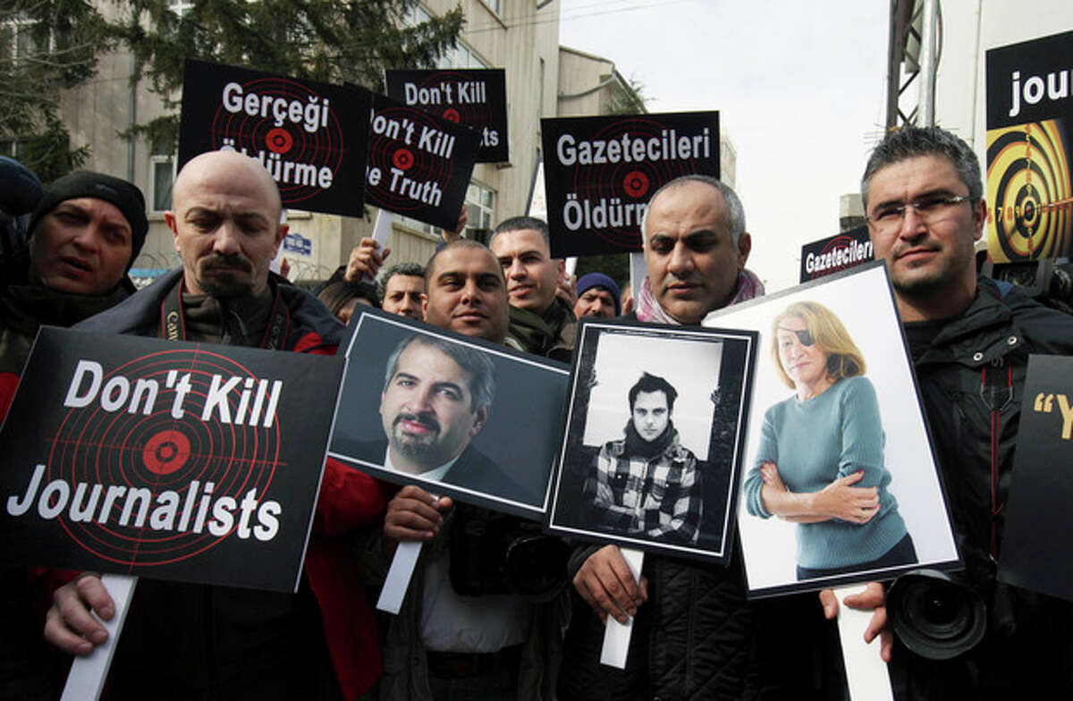 FILE - In this Feb. 24, 2012, file photo,Turkish journalists holding photographs of their colleagues who lost their lives in Syria recently, from left, Anthony Shadid, Remi Ochlik and Marie Colvin, stage a protest outside the Syrian Embassy in Ankara. Behind a veil of secrecy, at least 30 journalists have been kidnapped or have disappeared in Syria ?- held and threatened with death by extremists or taken captive by gangs seeking ransom. (AP Photo/Burhan Ozbilici, File)