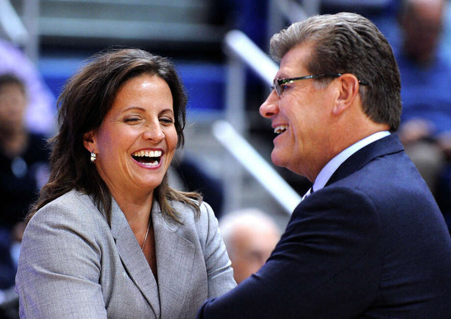 Connecticut coach Geno Auriemma speaks with Hartford coach Jennifer Rizzotti before an NCAA college basketball game in Hartford, Conn., on Saturday, Nov. 9, 2013. (AP Photo/Fred Beckham) / FR153656 AP