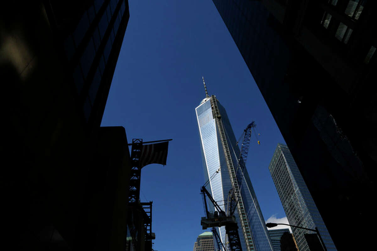 FILE - This Sept. 22, 2013 file photo shows a partial view of One World Trade Center, a skyscraper built at the site of the 9/11 attacks on the World Trade Center in New York. Soaring above the city at 1,776 feet, 104-story One World Trade Center is in contention with Chicago's Willis Tower for the title of America's tallest building. A committee of architects recognized as the arbiters on world building heights is meeting Friday Nov. 8, 2013 in Chicago to decide whether a design change affecting One World Trade Center's needle disqualifies its hundreds of feet from being counted, which would deny the building the title of nation?'s tallest giving the title to the 110 story Willis Tower at 1,450 feet. (AP Photo/Lefteris Pitarakis)