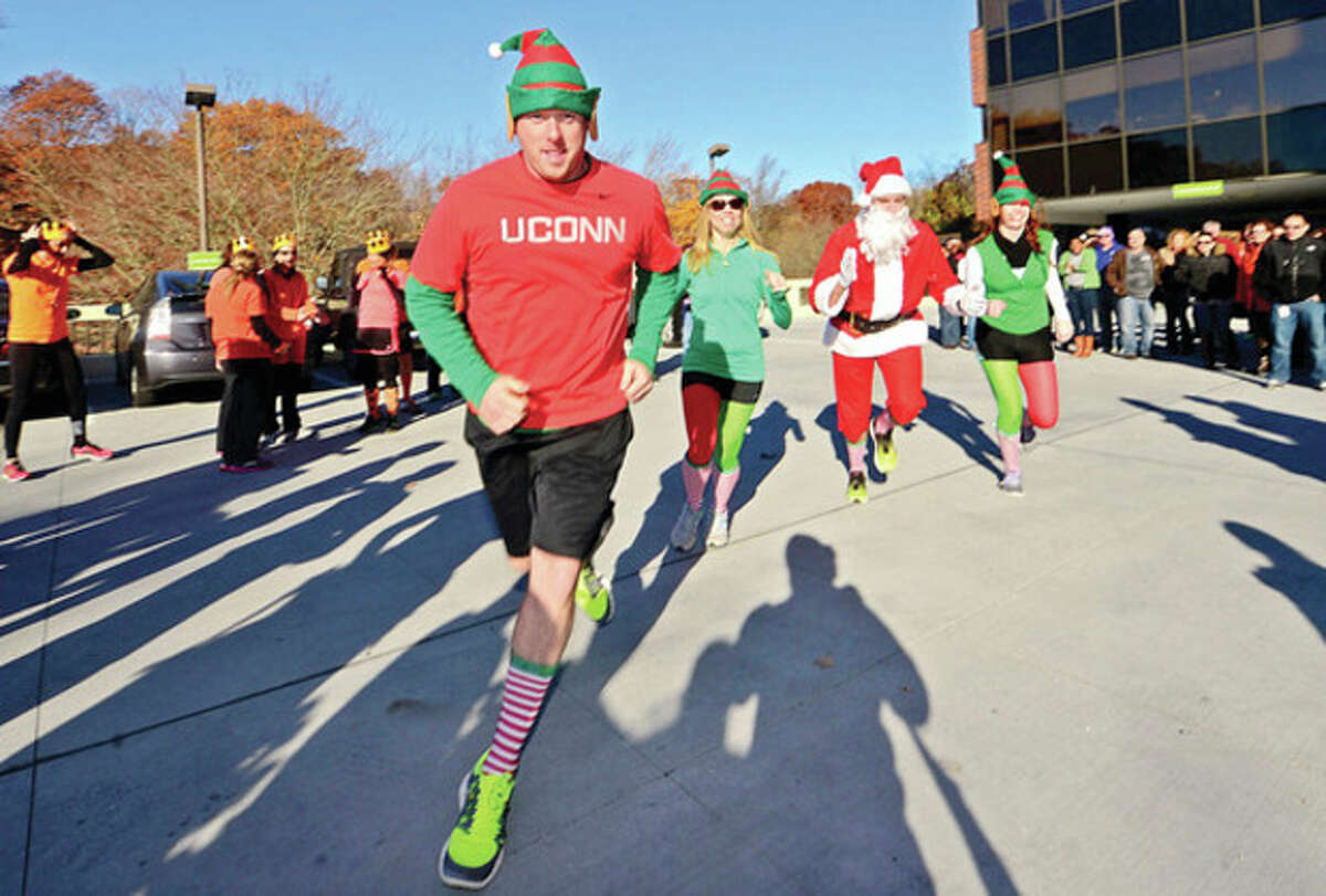 Hour photo / Erik Trautmann Ryan Fanning leads his team, Santa's Speed Demons, in Reed Exhibitions annual 5K run for charity Friday benefiting the Bridgeport Rescue Mission.