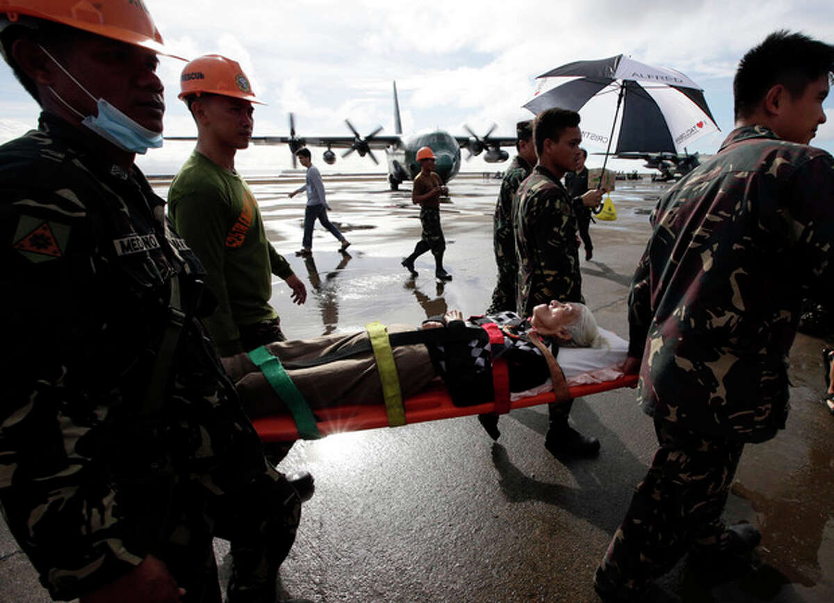 An injured typhoon survivor is carried on a stretcher prior to being airlifted in a military transport plane Wednesday Nov. 13, 2013 from the damaged Tacloban airport at Tacloban city, Leyte province in central Philippines. Typhoon Haiyan, one of the strongest storms on record, slammed into central Philippine provinces Friday, leaving a wide swath of destruction and thousands of people dead. (AP Photo/Bullit Marquez)