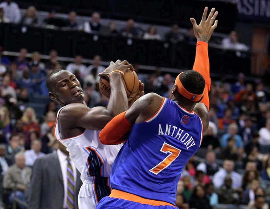 Charlotte Bobcats center Bismack Biyombo, left, battles New York Knicks forward Carmelo Anthony in the first half of an NBA basketball game in Charlotte, N.C., Friday, Nov. 8, 2013. (AP Photo/Nell Redmond) / FR25171 AP