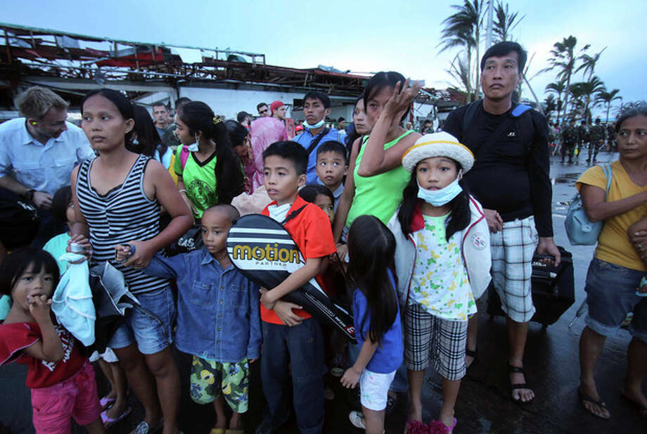 Survivors of Typhoon Haiyan wait at the airport in hopes of being evacuated on C-130 cargo planes, Tuesday, Nov. 12, 2013 in Tacloban city, Leyte province, central Philippines. Four days after Typhoon Haiyan struck the eastern Philippines, assistance is only just beginning to arrive. (AP Photo/Wong Maye-E) / AP