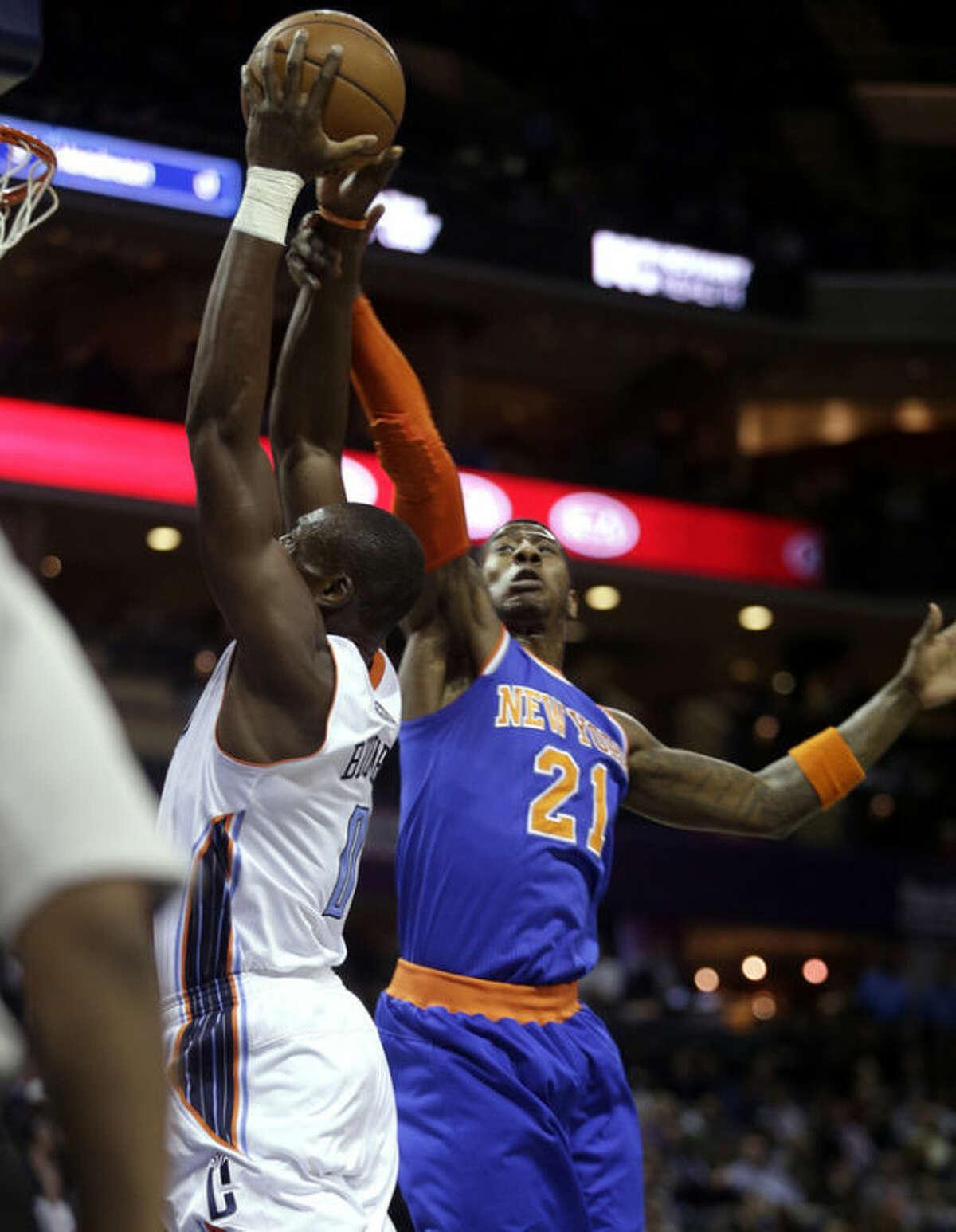 New York Knicks guard Iman Shumpert, right, fouls Charlotte Bobcats center Bismack Biyombo in the first half of an NBA basketball game in Charlotte, N.C., Friday, Nov. 8, 2013. (AP Photo/Nell Redmond)