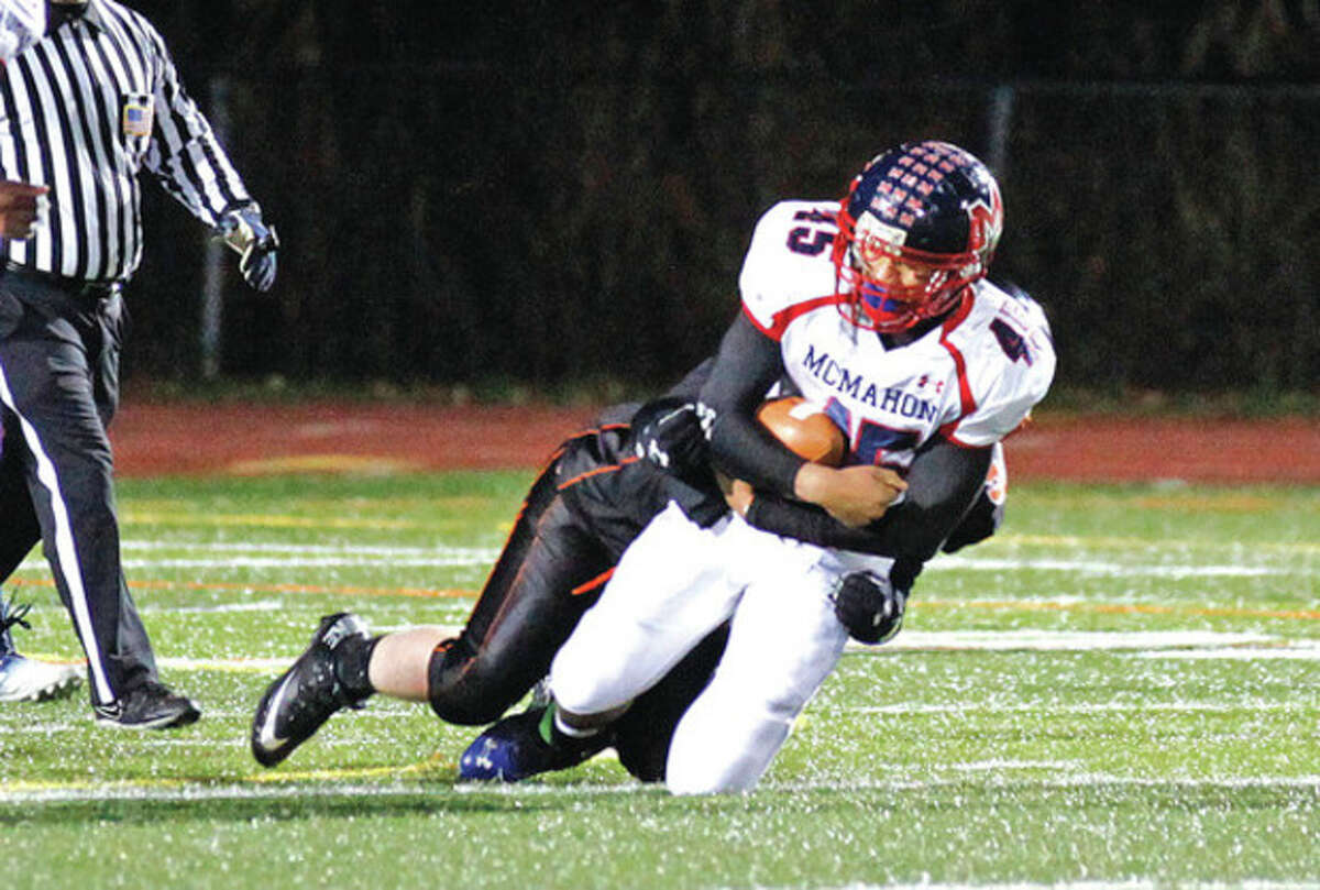 Hour photo/Danielle Calloway Brien McMahon's Kenny Keen is brought down by a Ridgefield defender during Friday night's game at Tiger Hollow. Ridgefield handed previously unbeaten McMahon a 44-7 defeat.