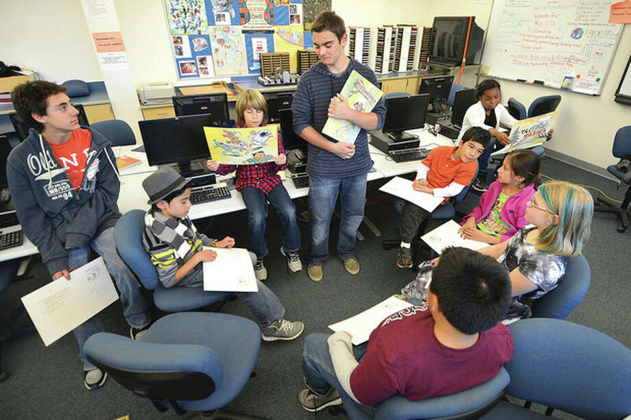 """Hour Photo / Alex von KleydorffCenter for Global Studies student Quinten Yonkers has Brookside students read one panel each of the Japanese children's book """"The Goblin, the Water Nymph and the Thundergod"""" during a reading program with students atBrookside Elementary School."""