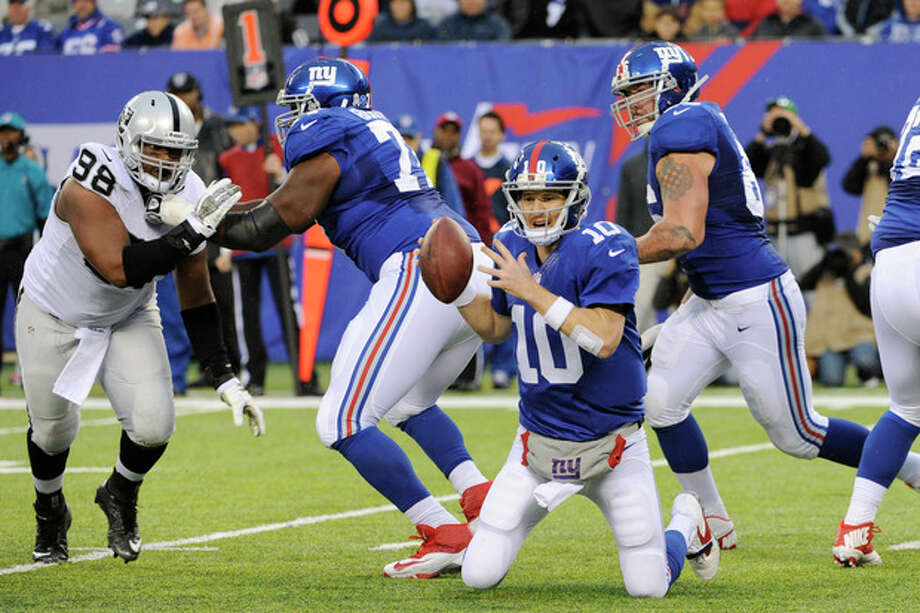 New York Giants quarterback Eli Manning (10) falls to his knees while trying to avoid being hit during the first half of an NFL football game against the Oakland Raiders, Sunday, Nov. 10, 2013, in East Rutherford, N.J. (AP Photo/Bill Kostroun) / FR51951 AP
