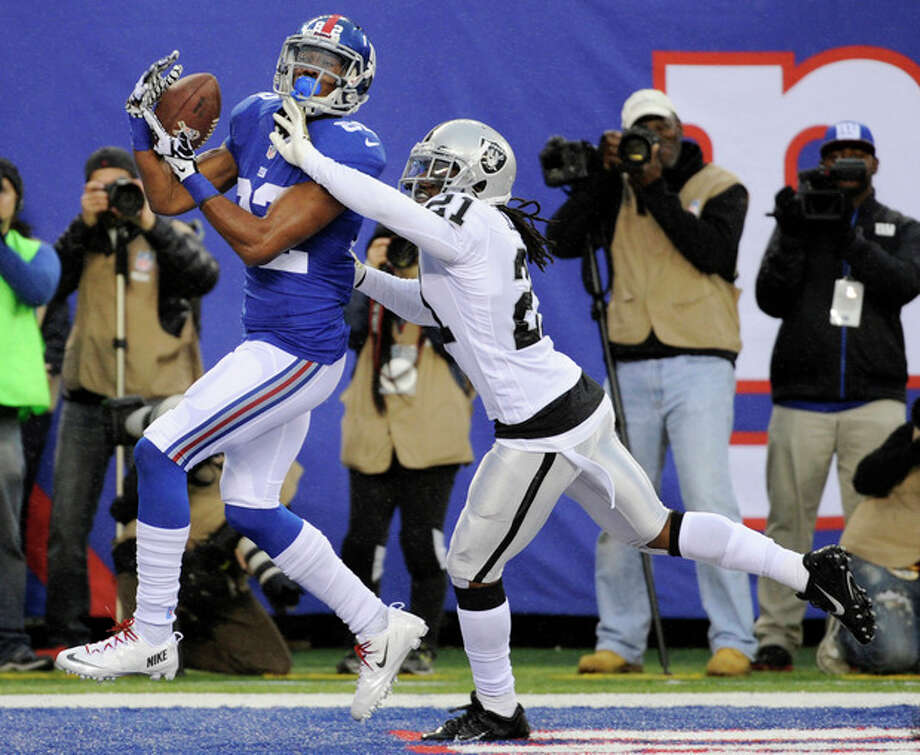 New York Giants wide receiver Rueben Randle, left, catches a touchdown pass as Oakland Raiders cornerback Mike Jenkins (21) defends on the play during the first half of an NFL football game on Sunday, Nov. 10, 2013, in East Rutherford, N.J. (AP Photo/Bill Kostroun) / FR51951 AP