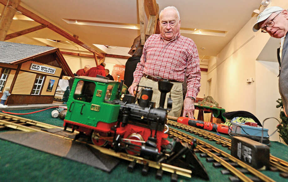 Hour photo / Erik Trautmann Wilton Historical Society volunteer Ivan Spangenberg, center, helps prepare for the first annual Holiday Trunk Show and Great Trains Holiday Exhibit. The trunk show wil sell handcrafted merchandise from six local vendors at the society's Betts Store.