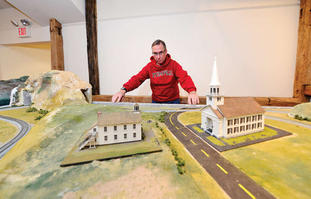 Hour photo / Erik Trautmann Wilton Historical Society volunteer Paul Lourd, center, helps prepare for the first annual Holiday Trunk Show and Great Trains Holiday Exhibit. The train exhibit will feature donated antique model train sets in a variety of gauges.