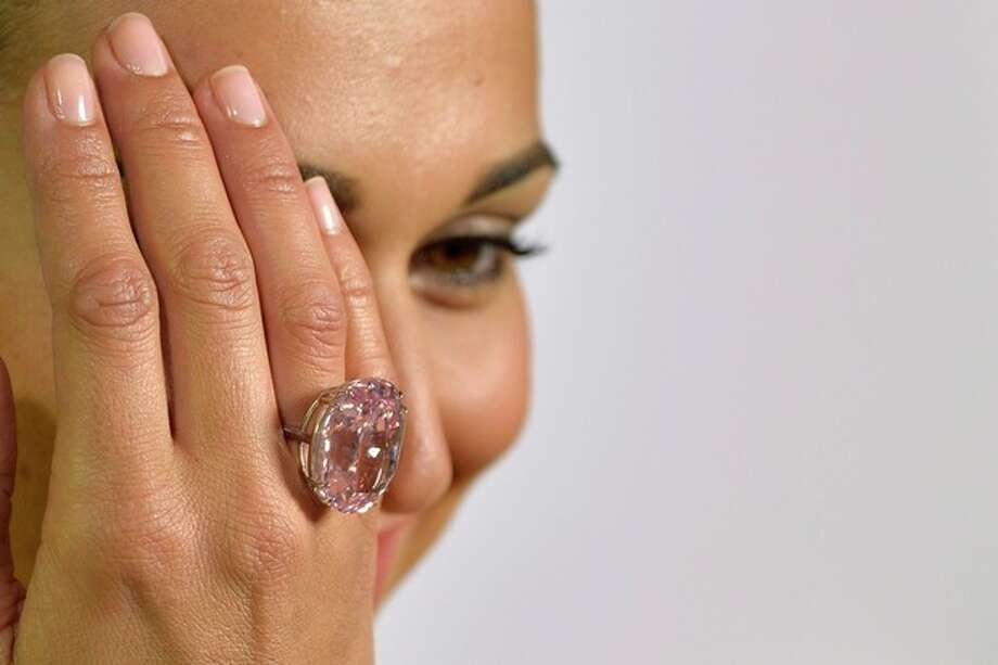 "FILE - A Wednesday, Sept. 25, 2013 photo from files showing an unidentified Sotheby's employee displaying ""The Pink Star"" diamond weighing 59.6 carat, during a preview at Sotheby's, in Geneva, Switzerland. Wednesday, September 25, 2013. The enormous diamond has sold for $83.425 million (61.8 million euro) at an auction, Wednesday night, Nov. 13, 2013, far surpassing its expected price. Sotheby's says the sale of the vivid and flawless 59.60-carat pink diamond is the highest price ever paid for a gemstone at auction. (AP Photo/Keystone, Martial Trezzini, File) / KEYSTONE"