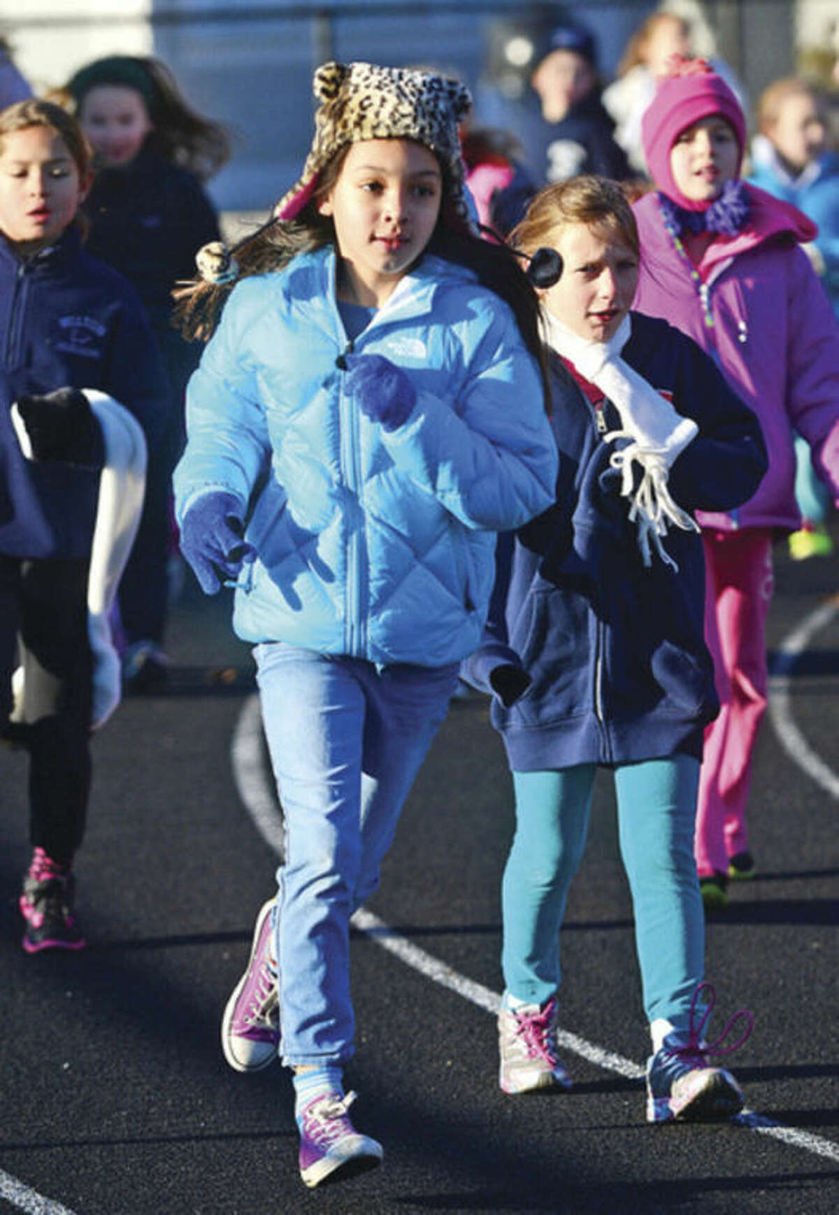 Hour photo / Erik Trautmann Cider Mill Elementary School 3rd grader Sammy Slough, center, and her class participate in the school's annual Turkey Trot run Thursday to raise money for Wilton Social Services.