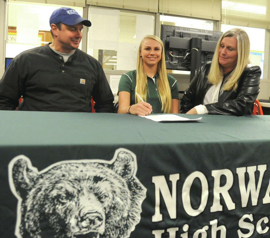 Hour photo/John NashNorwalk High senior swimmer Lauren Czulewicz sits between her parents Don and Ellie before she signs an official national letter of intent to compete at Central Connecticut State University next year.