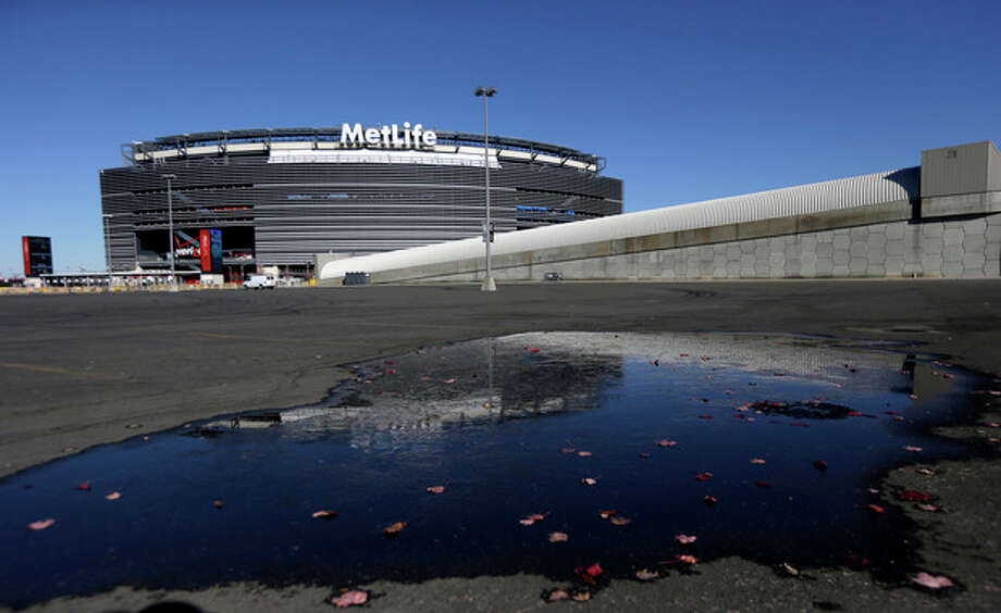 "In this photo taken on Wednesday, Nov. 13, 2013, a sheet of ice forms over a puddle on the parking lot at MetLife Stadium in East Rutherford, N.J. Northern New Jersey towns hoping to get Super Bowl visitors to spend time and money in the Garden State and not just across the river in Manhattan, realize they need to come up with a creative game plan to separate itself from New York. There's a catch: None of the festivities can employ the words ""Super Bowl,"" a name that is trademarked by the NFL. (AP Photo/Julio Cortez) / AP"