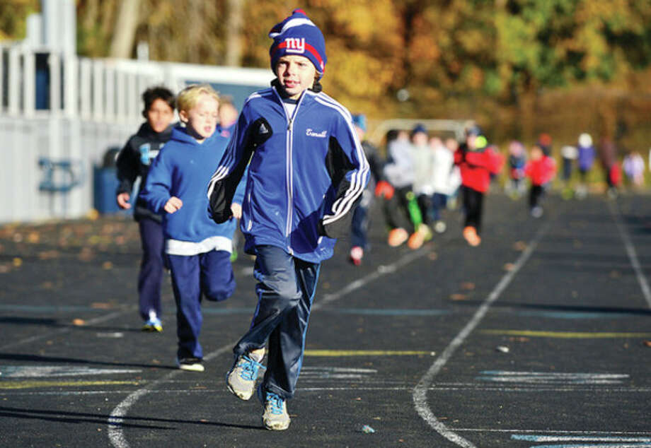 Hour photo / Erik Trautmann Cider Mill Elementary School 3rd grader Wilson Tansill participates with his class in the school's annual Turkey Trot run Thursday to raise money for Wilton Social Services. / (C)2013, The Hour Newspapers, all rights reserved