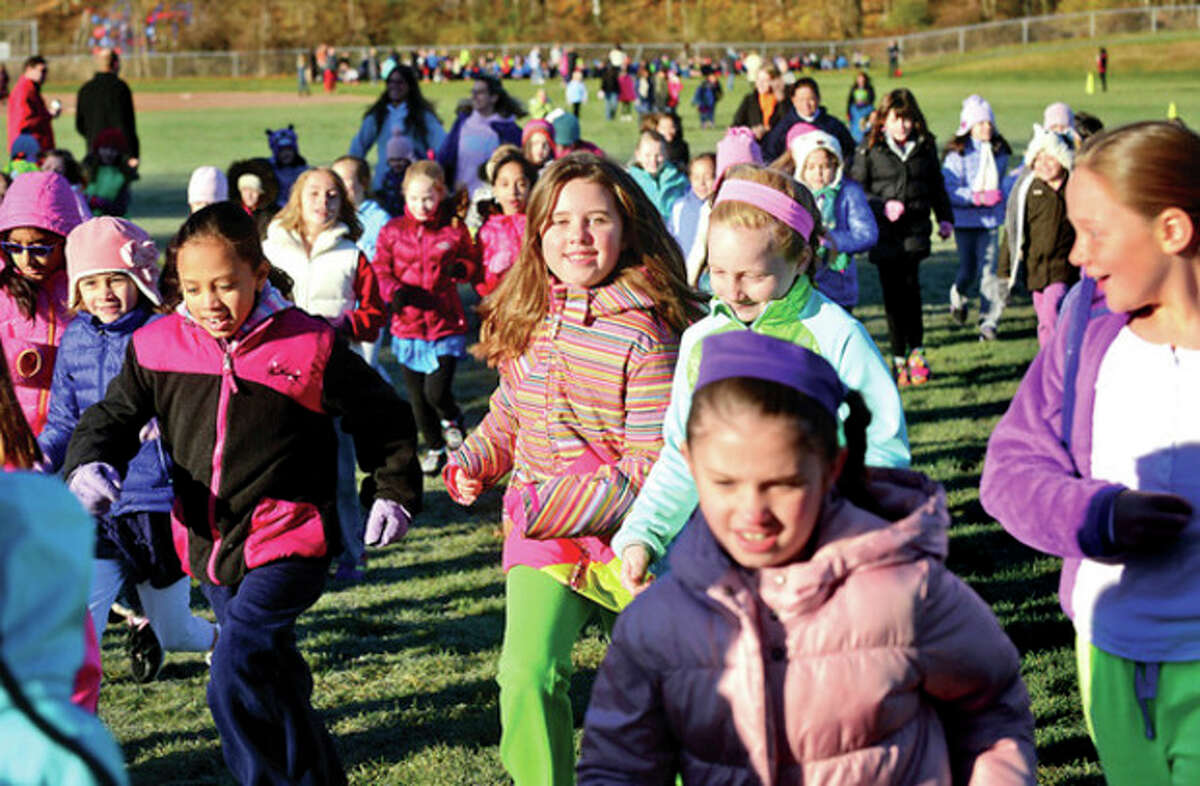 Hour photo / Erik Trautmann Cider Mill Elementary School 3rd grader Skylar Garvin, center, and her class participate in the school's annual Turkey Trot run Thursday to raise money for Wilton Social Services.