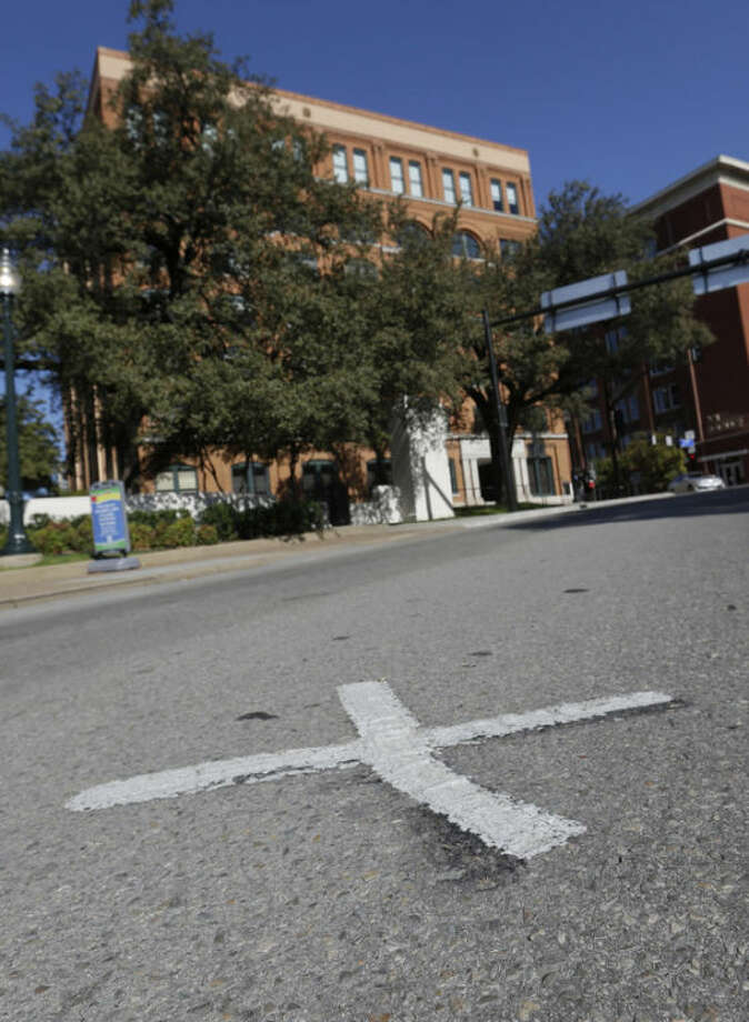 An X marks the spot on Elm Street on Tuesday, Nov. 12, 2013 where the first bullet hit President John F. Kennedy on Nov. 22, 1963 near the former Texas School Book Depository, now known as the Sixth Floor Museum, background, on Dealey Plaza in Dallas. (AP Photo/LM Otero)