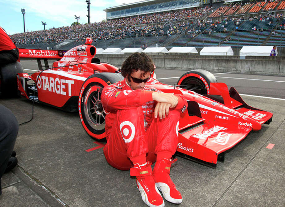 FILE - In this Sept. 17, 2011, file photo, IndyCar driver Dario Franchitti, of Scotland, sits by his car during the qualifying of the Indy Japan auto race at Twin Ring Motegi in Motegi, northeast of Tokyo, Japan. The three-time Indianapolis 500 winner said Thursday, Nov. 14, 2013, that doctors have told him he can no longer race because of injuries sustained in an IndyCar crash last month. He fractured his spine, broke his right ankle and suffered a concussion in the Oct. 6 crash at Houston. (AP Photo/Shizuo Kambayashi, File) / AP