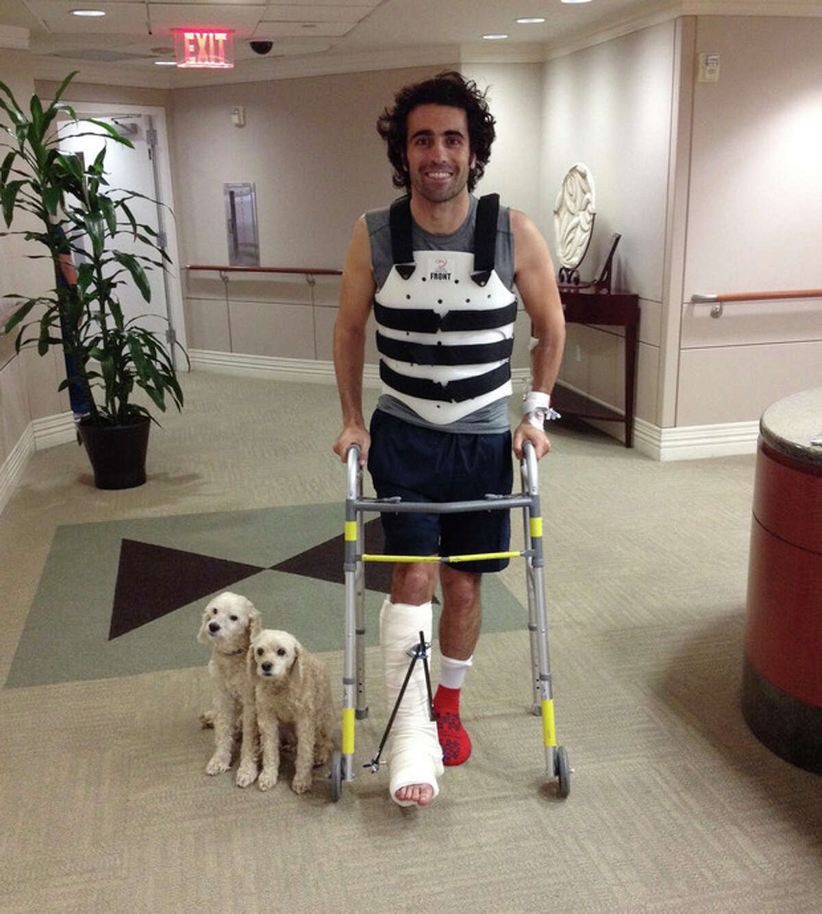 FILE - In this Oct. 10, 2013, file photo, provided by Team Chip Ganassi Racing, IndyCar driver Dario Franchitti, of Scotland, poses with his dogs, Shug and Buttermilk, in a photo taken by his brother, Marino Franchitti, at Memorial Hermann-Texas Medical Center in Houston. The three-time Indianapolis 500 winner said Thursday, Nov. 14, 2013, that doctors have told him he can no longer race because of injuries sustained in an IndyCar crash last month. He fractured his spine, broke his right ankle and suffered a concussion in the Oct. 6 crash at Houston. (AP Photo/Marino Franchitti, File)