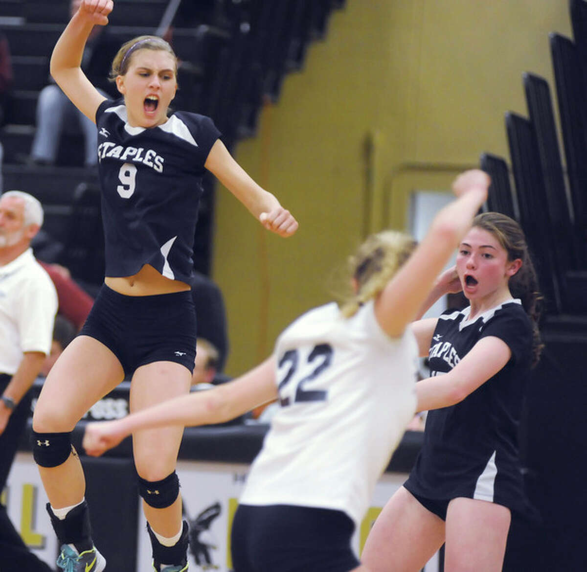 Hour photo/John Nash Staples volleyball players, from left, Lauren Mushro (9), Valerie Kirsch (22) and Ariana Sherman celebrate a point in the clinching set of Thursday's 3-1 win over Greenwich in a CIAC Class LL semifinal in Trumbull.