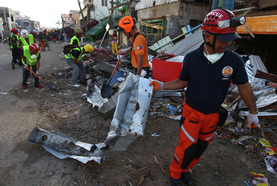 Filipino rescue workers clear a street from debris caused by Typhoon Haiyan in Guiuan, Philippines, Friday, Nov. 15, 2013. Typhoon Haiyan, one of the most powerful storms on record, hit the country's eastern seaboard on last Friday, destroying tens of thousands of buildings and displacing hundreds of thousands of people. (AP Photo/Dita Alangkara) / AP