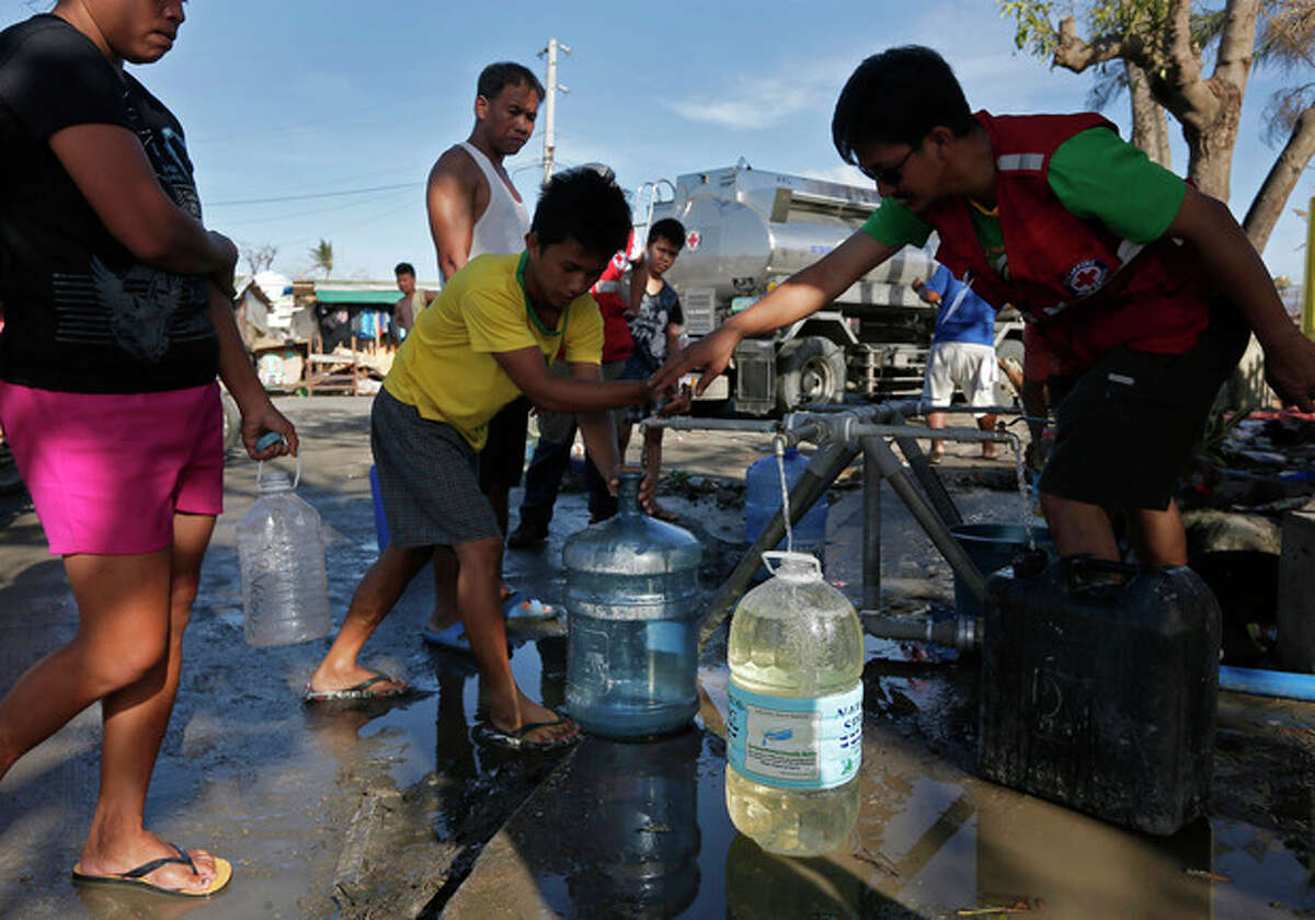 Red Cross workers deliver clean water to survivors at a medical center in the city of Tacloban, Philippines Friday, Nov. 15, 2013. Thirsty residents have been struggling to find clean water since Typhoon Haiyan hit, resorting to drinking from broken pipes, rivers and any taps that remain working. (AP Photo/Vincent Yu)