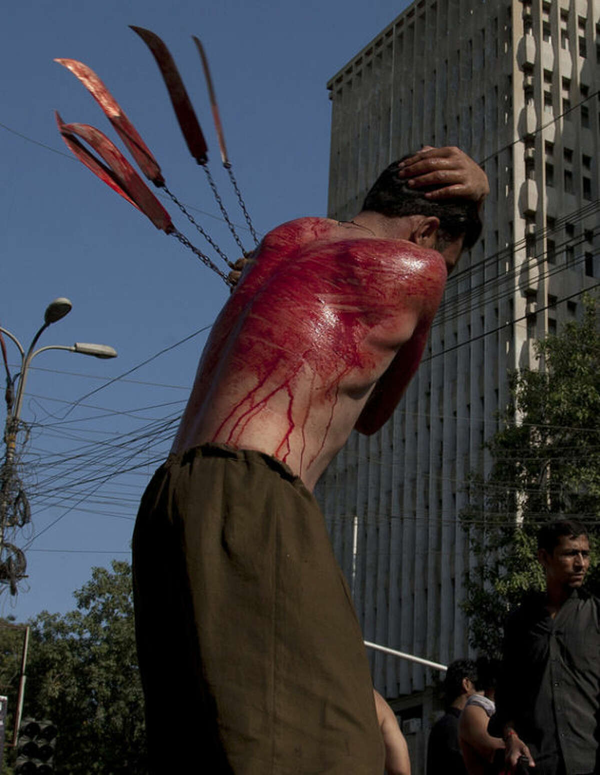 A Pakistani Shiite Muslim beats himself with knives attached to a chain during an Ashoura procession in Karachi, Pakistan, Friday, Nov. 15, 2013. Ashoura commemorates the martyrdom of Imam Hussein, the grandson of Prophet Muhammad at the Battle of Karbala, Iraq, in the year 680 A.D. (AP Photo/Shakil Adil)