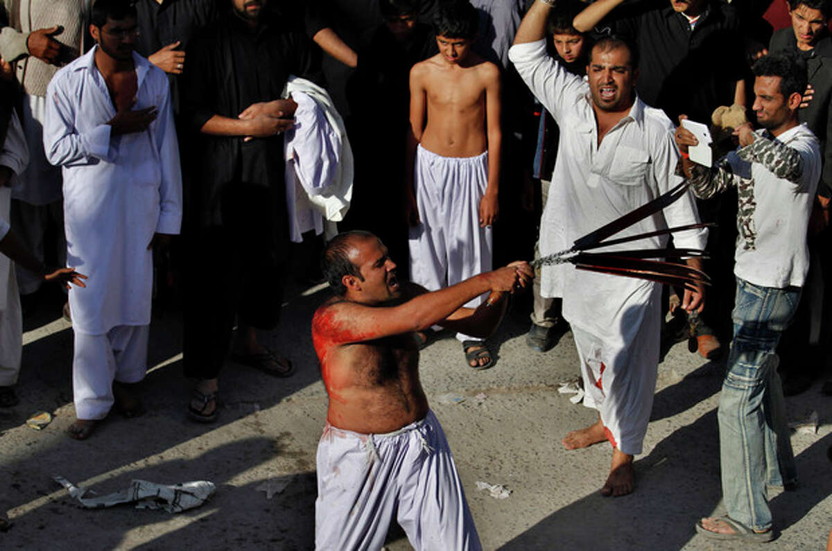 A Pakistani Shiite Muslim flagellates himself with knives attached to a chain during an Ashoura procession in Rawalpindi, Pakistan, Friday, Nov. 15, 2013. Ashoura commemorates the martyrdom of Imam Hussein, the grandson of Prophet Muhammad at the Battle of Karbala, Iraq, in the year 680 A.D. (AP Photo/Anjum Naveed)