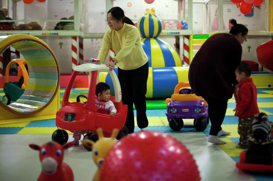 FILE - In this Jan. 10, 2013 photo, parents play with their children at a kid's play area in a shopping mall in Beijing. China will loosen its decades-old one-child policy and abolish a much-criticized labor camp system, its ruling Communist Party said Friday, Nov. 15, 2013. The official Xinhua News Agency said the party announced the changes in a policy document following a key, four-day meeting of party leaders that ended Tuesday in Beijing. (AP Photo/Alexander F. Yuan, File) / AP