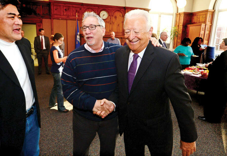 Hour photo / Erik Trautmann City Hall employees Alan Lo and Rick McQuaid say goodbye to Mayor Richard A. Moccia during afternoon luncheon in Comunity Room of Norwalk City Hall on Friday