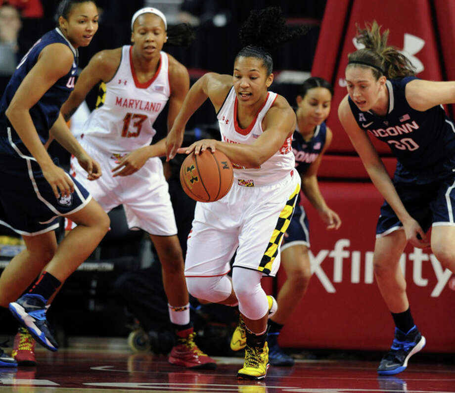 Maryland's Alyssa Thomas, center, grabs a rebound ahead of Connecticut's Breanna Stewart, right, in the first half of an NCAA basketball game Friday, Nov. 15, 2013 in College Park, Md.(AP Photo/Gail Burton) / FR4095 AP