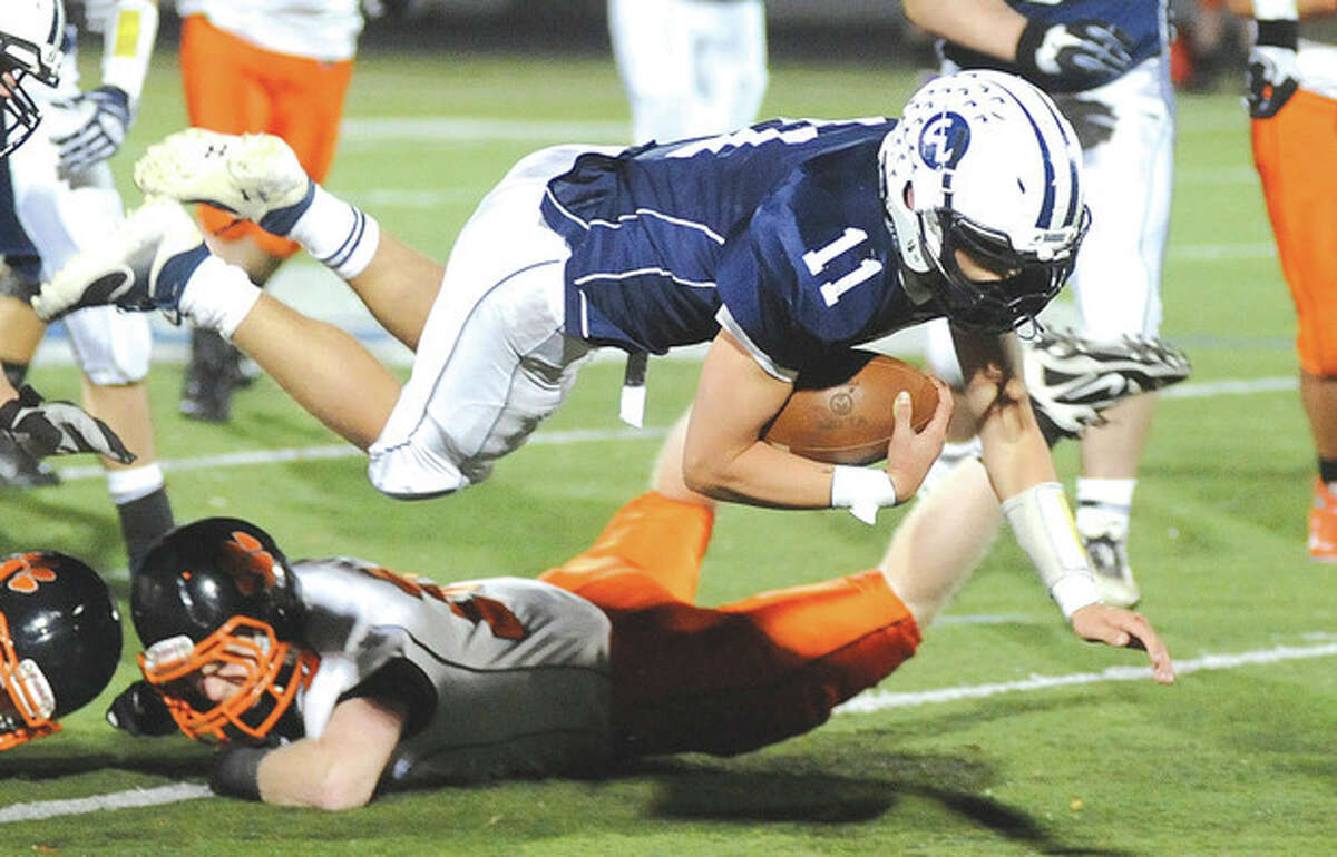 Hour photo/John Nash Wilton quarterback Brett Phillips (11) goes airborne over the Ridgefield defense as he looks to pick up a few extra yards on a rush during Friday's game at Fujitani Field in Wilton.