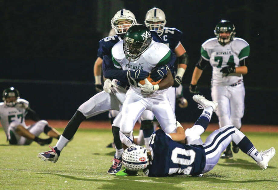 Hour photo/Chris PalermoNorwalk High's Cliff Joseph runs through the Staples defense during Friday night's game in Westport. / © 2013 Hour Newspapers All Rights Reserved